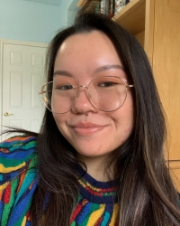 Picture of Mimi Louie wearing round gold rimmed glasses and a rainbow stripped sweater